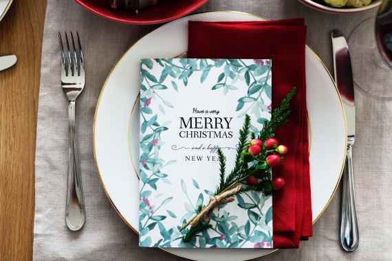 merry christmas card on plate between fork and knife